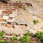 Render coming off brick wall